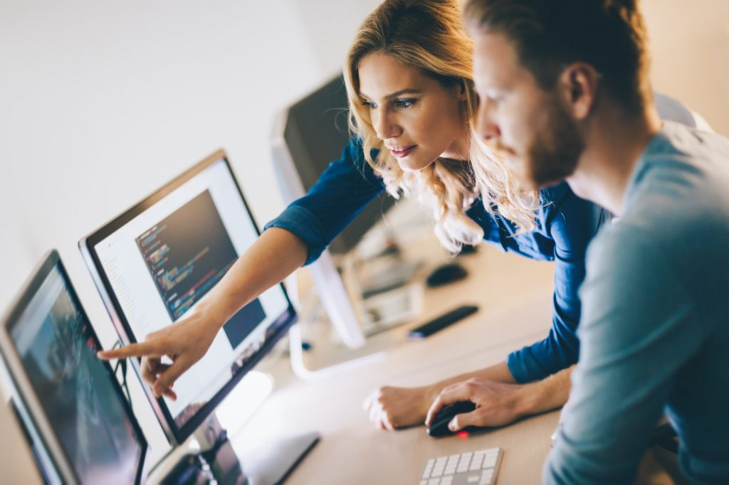 Technology professionals looking at computer monitors